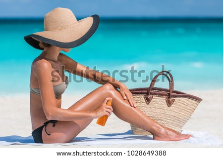 Sunscreen suntan lotion spray skincare product woman putting tanning oil on her legs. Sunblock or mosquito repellent bottle spraying on body sunbathing at beach summer vacation. #1028649388