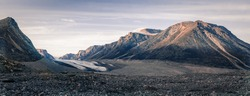 Sunset above above remote arctic valley of Akshayuk Pass, Baffin Island, Canada. Last rays of light on the peaks around Highway glacier. Arctic summer in the wild of the far north.