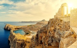 Sunset above Acropolis of Lindos. Doric columns the ancient Temple Athena Lindia the IV century BC and the bay St. Paul. Greece. Rhodes.