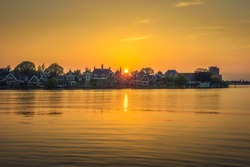 Sunset above the beautiful holland village of Zaanse Schans and the Zaan river near Amsterdam in the Netherlands.