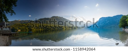 Sunset above the Bohinj lake, Slovenia. Magical evening color of sun with reflection in water. Julian Alps in background. Triglav national park.