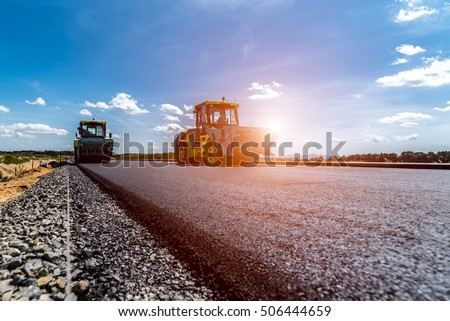 Sunset above the road roller working on the new road construction site #506444659