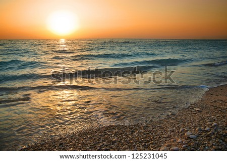 Sunset above the sea. Big sun and waves at beach