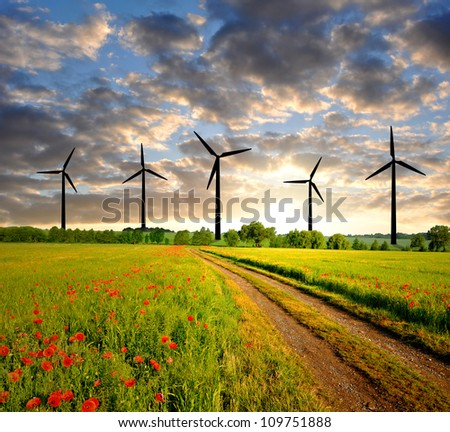 sunset above the spring landscape with wind turbines