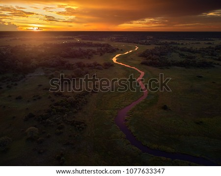 Sunset, aerial, atmospheric view on curving river Khwai, Moremi forest, Botswana. Typical ecosystem, part of Okavango delta, aerial photography. Vast wilderness without people, animal paradise.Africa.