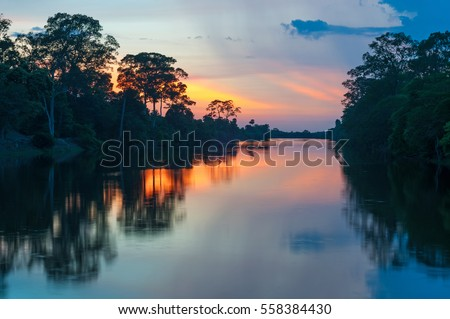Sunset along the banks of the Amazon river. The tributaries of the Amazon traverse the countries of Guyana, Ecuador, Peru, Brazil, Colombia, Venezuela and Bolivia.