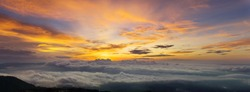 Sunset and Beautiful sky with clouds. Panorama of Fantastic foggy landscape glowing while sunrise in the morning. A beautiful landscape with high mountains foggy cover. Dense fog with beautiful light.