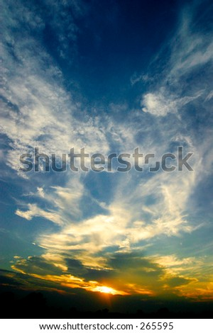 Sunset and blue sky with white clouds. Wide angle lens gives a sense of depth. Vertical format