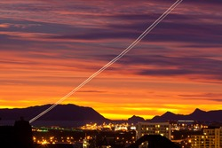 Sunset and light trail of starting airplane over Manukau  southern suburb of Auckland  New Zealand