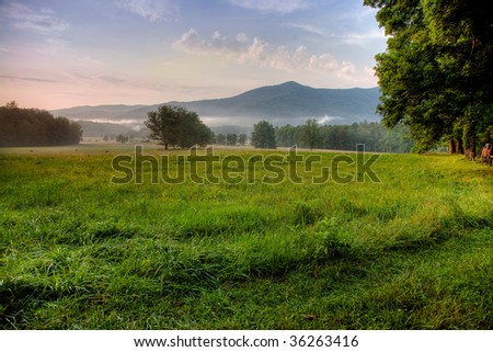 Sunset and mist highlight grassy landscape at Cades Cove