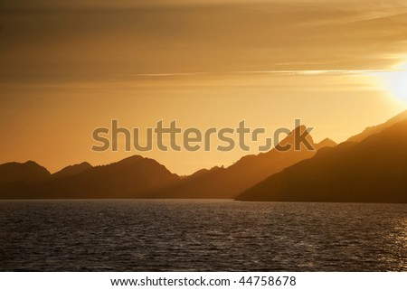 Sunset and mountain silhouette from the sea - stock photo