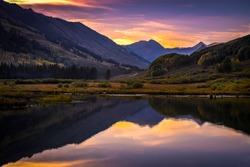 Sunset and mountains reflection on lake