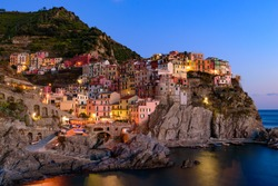Sunset and night view of Manarola, one of the five Mediterranean villages in Cinque Terre, Italy, famous for its colorful houses and harbor
