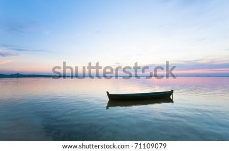 Sunset and old wooden fishing boat on summer lake bank (Svityaz, Ukraine)