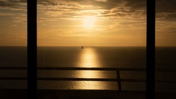 Sunset and sea view from room with flying bird through an open window and terrace fence. Summer holiday nature golden sky concept