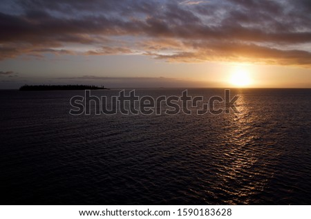 Sunset and small island near Ile Des Pins, New Caledonia, Overseas Territory of France