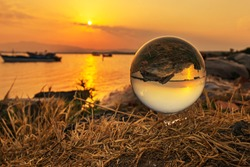 Sunset and tranquility Aliaga Izmir Turkey. Photo lens sphere focusing crystal sphere sun rays and magnifying and reflecting upside down background image.