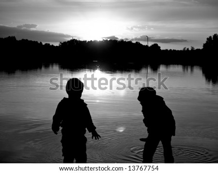 Sunset and two small young boys on the lake