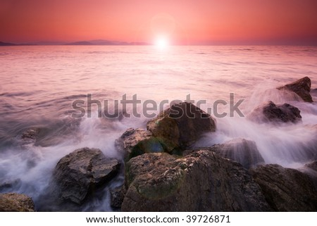Sunset and waves on the rocky shore of Aegean