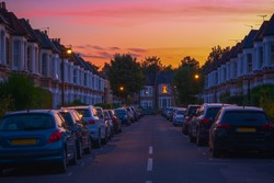 Sunset at a street of terraced houses with cars parked in resident bay around West Hampstead in London
