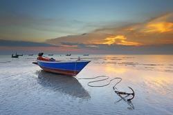Sunset at anchor fishing boat at low tide