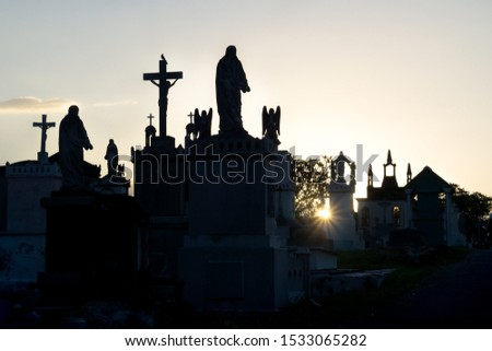 Sunset at cemetery with backlight and silhouettes of the tombs with drosses and Maria statues,Cementerio General, Merida, Mexico #1533065282