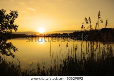 sunset at coast of the lake - stock photo
