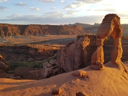 Sunset at delicate arch viewpoint in Arches nationalpark in Utah USA with red sandstone rock arch formation in evening light / sunlight