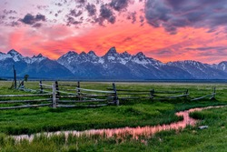 Sunset at Grand Teton - A panoramic view of a spectacular spring sunset at Teton Range, seen from an abandoned old ranch in Mormon Row historic district, in Grand Teton National Park, Wyoming, USA.
