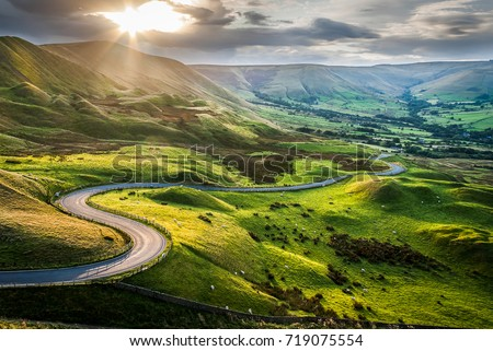 Sunset at Mam Tor, Peak District National Park, with a view along the winding road among the green hills down to Hope Valley, in Derbyshire, England.