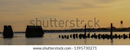 Sunset at old Blaine, Washington pier showing the pilings and concrete piers once used by lumber and salmon cannery ships, shown in silhouette against a golden sunset, marina and iconic water tower #1395730271