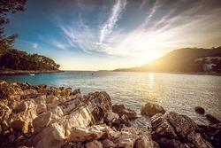 Sunset at rocky stone beach at Korcula island in Croatia. Adriatic sea.