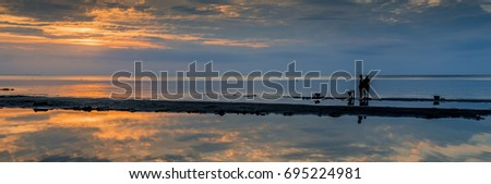 Sunset at sandy beach of the Baltic Sea, time of summer vacation