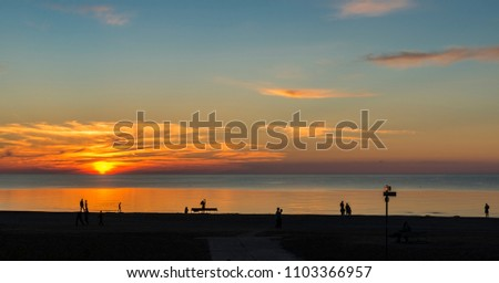 Sunset at sandy beach of the Baltic Sea, time of summer vacation. Jurmala, Latvia