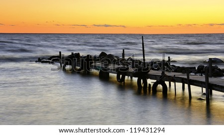 Sunset at sea behind wooden boat bridge with old tires