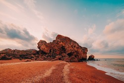 Sunset at sea. Scenic view of the sea, rocky coastline and sandy beach, golden sky and sun, outdoor travel background. General's beaches. Crimea.