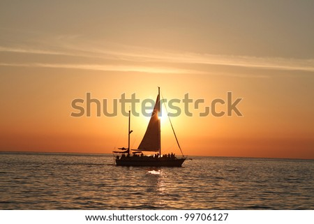Sunset at sea with a sailboat.