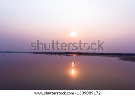 sunset at small lake in Thailand with man in fishing boat, silhouette fishing boat in dam at evening time, minimal subject and landscape picture in wind angle view