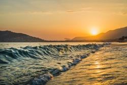 Sunset at the beach in Alanya, Turkey. View of the castle hill and sea, evening light