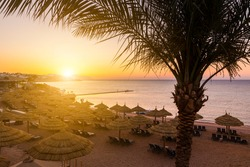 Sunset at the beach with palm trees, parasols and sunbeds.