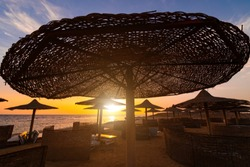 Sunset at the beach with palm trees, parasols and sunbeds. Family Holidays at Sea.