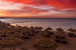 Sunset at the beach with palm trees, parasols and sunbeds. Family Holidays at Sea. Red Sea, Egypt.