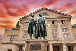 Sunset at the famous German National Theater with Goethe-Schiller Monument in Weimar, Thuringia, Germany
