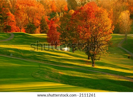 Sunset at the Golf Course - The sunset casts a brilliant glow on the red and gold foliage of the trees at a Kentucky USA golf course in Autumn.
