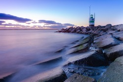 Sunset at the IJmuiden southern pier with  the green and white lighthouse  during blue hour with a long exposure and water ond the rocks.