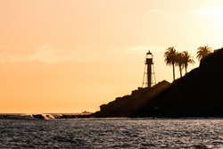 Sunset at the new Point Loma lighthouse in San Diego, California with waves and palm trees.