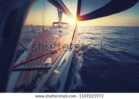 Sunset at the Sailboat deck while cruising / sailing at opened sea. Yacht with full sails up at the end of windy day. Sailing theme - background. Yachting background design.