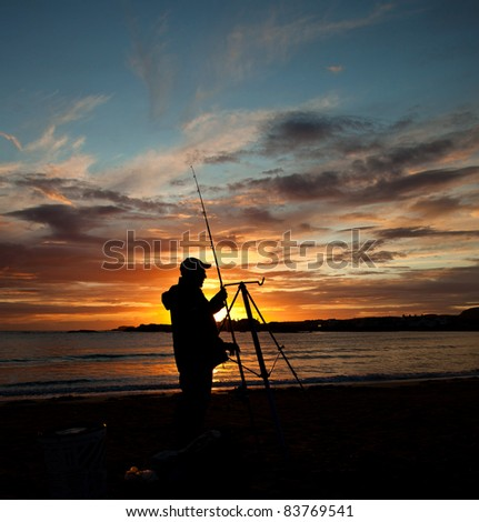 Sunset at Trearddur bay with a fisherman setting out his rod Isle of Anglesey
