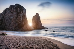 Sunset at Ursa Beach Sea stack, Portugal. Atlantic Ocean Foamy waves rolling to sandy beach. Holiday vacation landscape scene