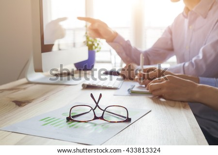 Sunset atmosphere in co-working office, business meeting with two people, close-up on glasses